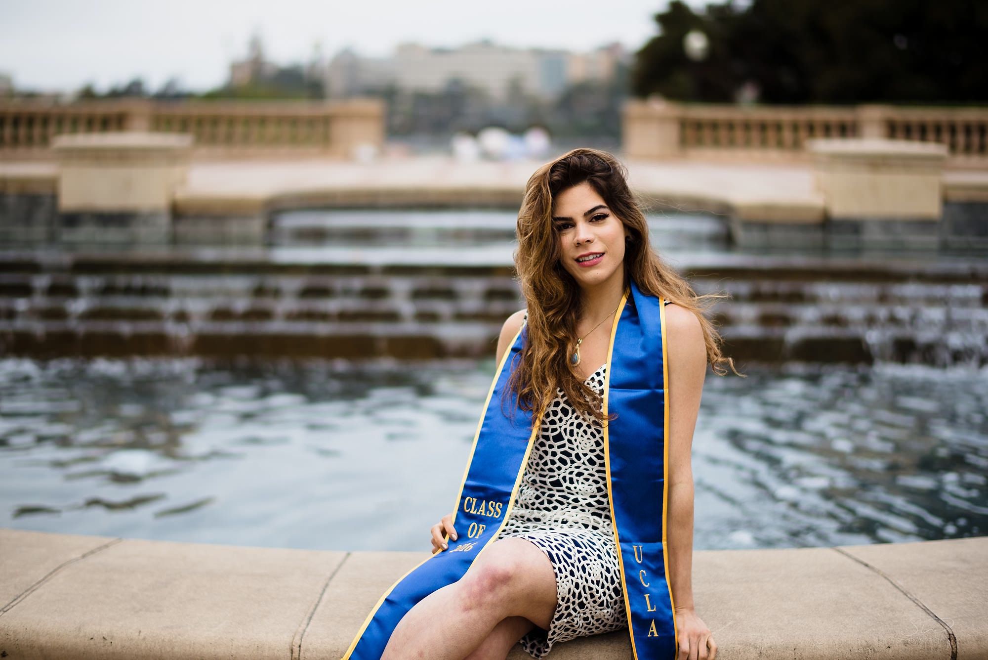 los angeles graduation senior portrait of a girl sitting elegantly in front of a fountain at ucla