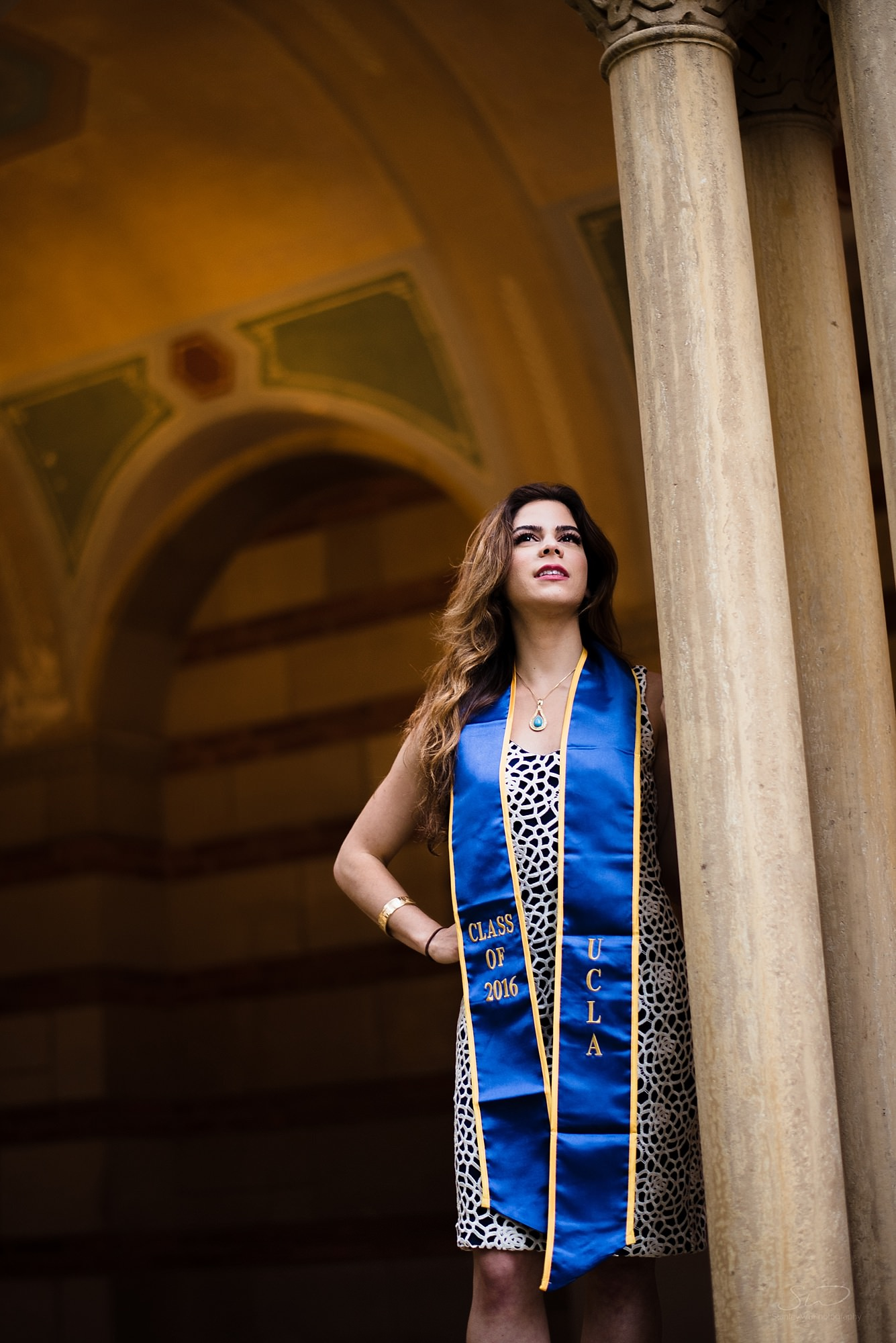 epic graduation senior portrait of a girl standing heroically next to a pillar at ucla in los angeles