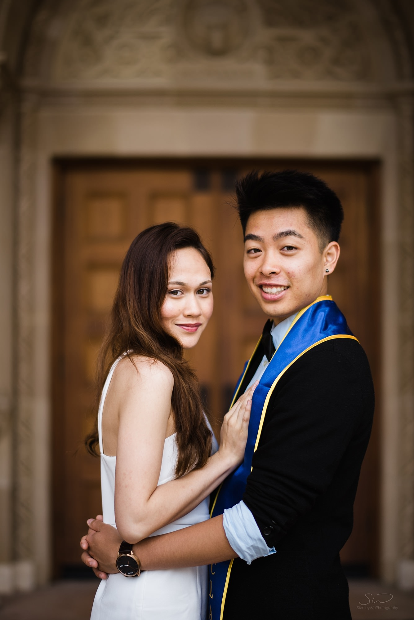 cute graduation senior portrait of a couple in each others arms looking at the camera at ucla in los angeles