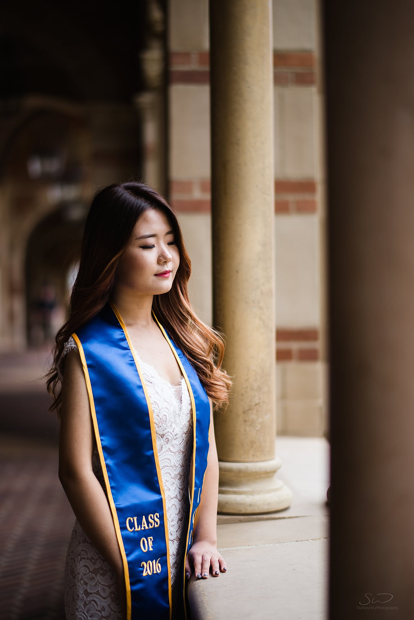beautiful graduation senior portrait of a girl looking down with radiant light shining on her at ucla in los angeles