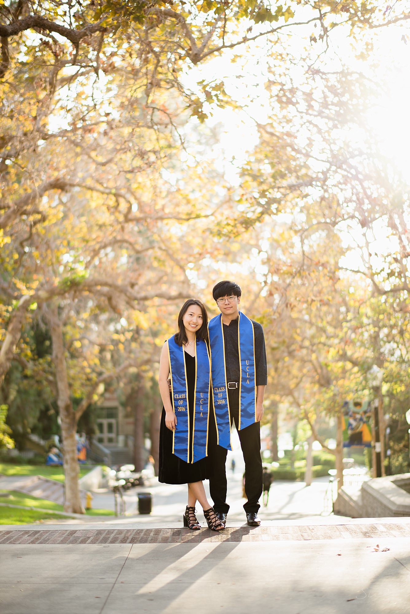 pretty graduation senior portrait of a couple standing on bruinwalk with an epic sunset making trees glow orange at ucla in los angeles