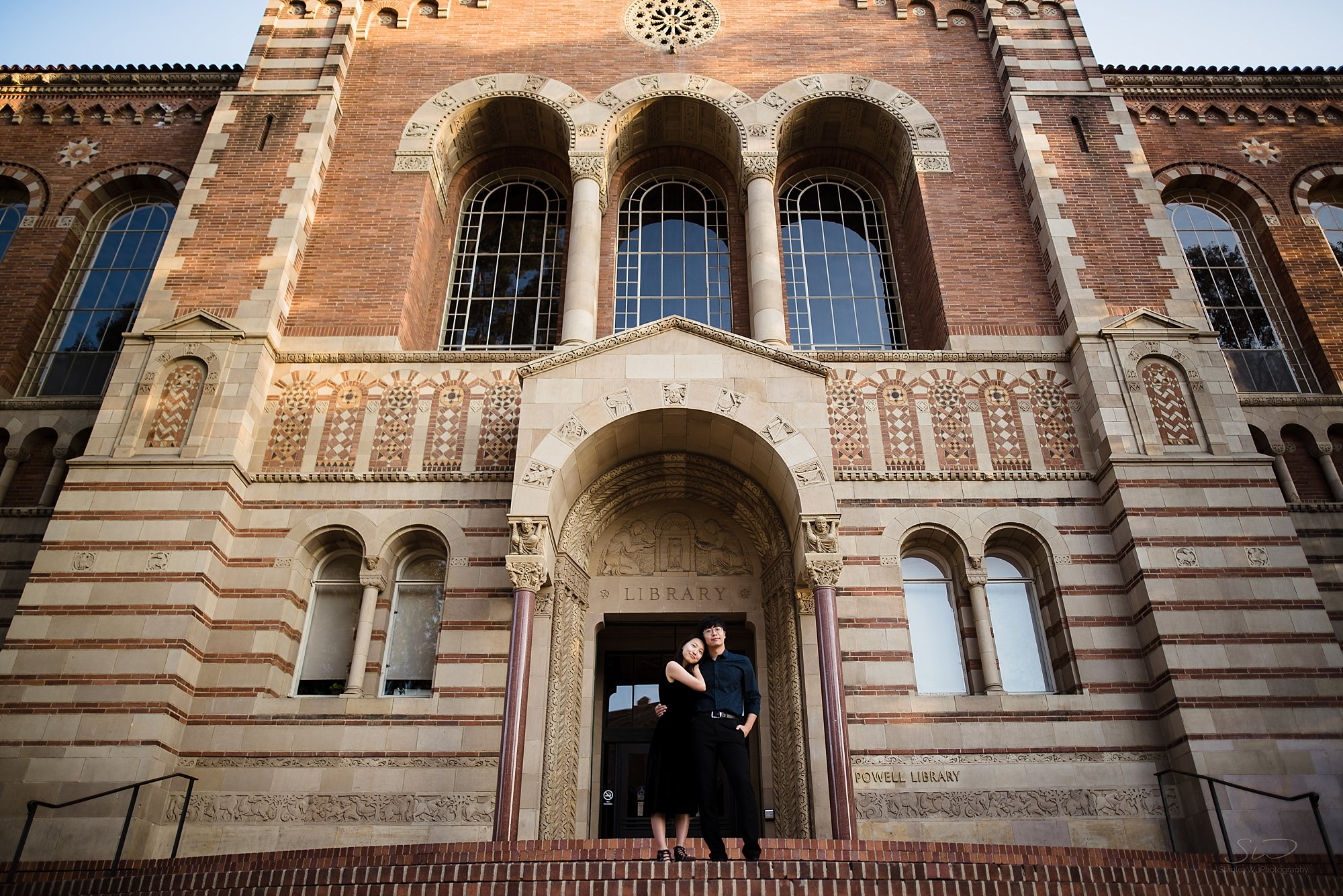 graduation senior portrait of a couple in love wearing black standing in front of powell library at ucla in los angeles