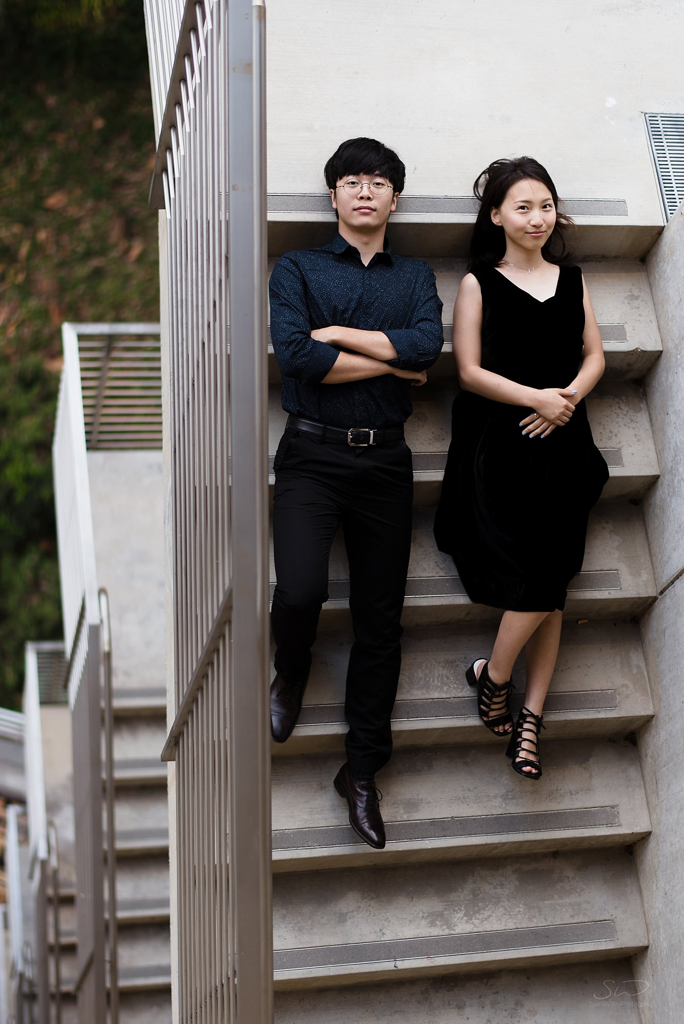 artistic graduation senior portrait shot from top down of a fashionable couple wearing black lying on stairs at ucla in los angeles