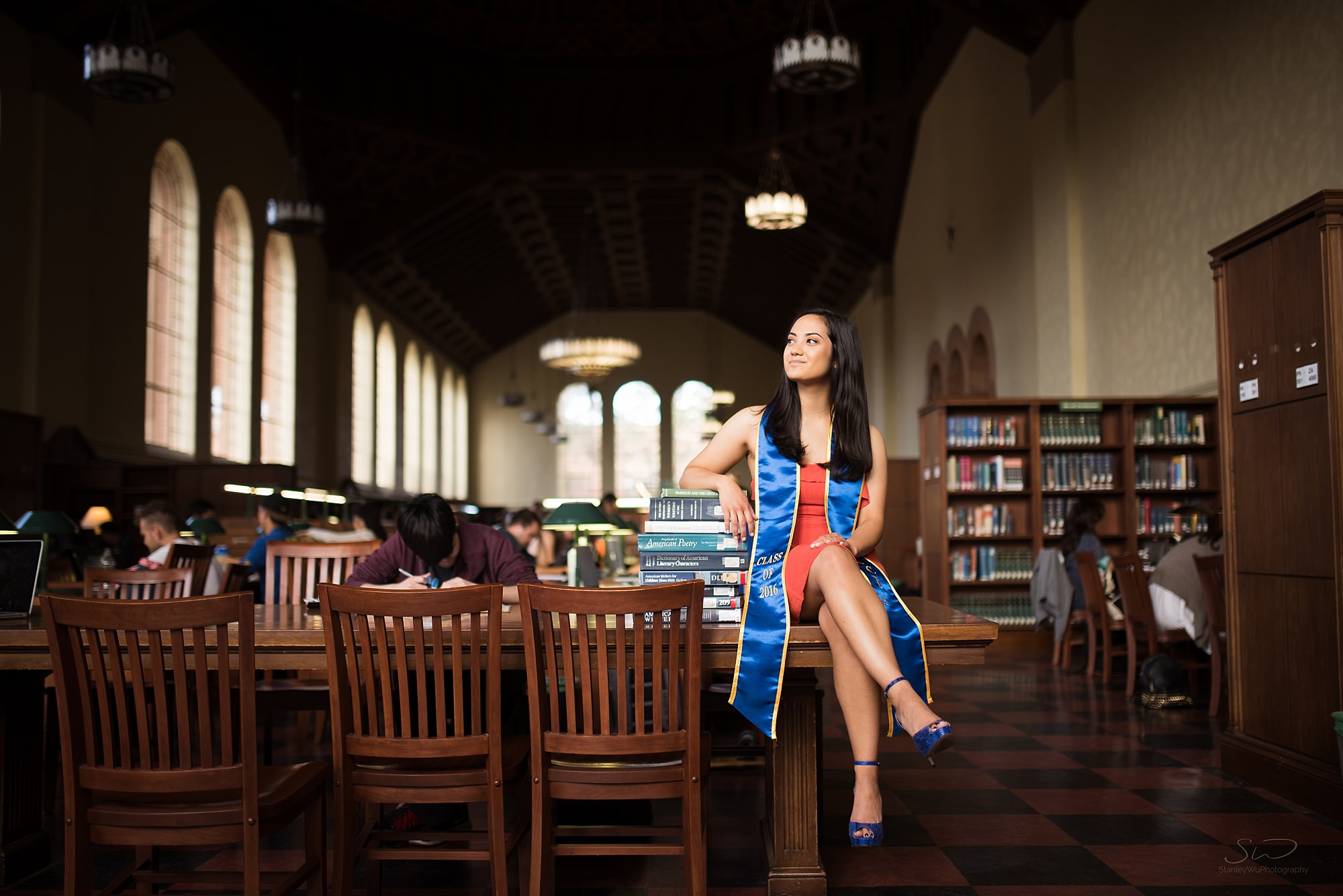 beautiful graduation senior environmental portrait of a girl sitting in a natural spotlight in powell library at ucla in los angeles