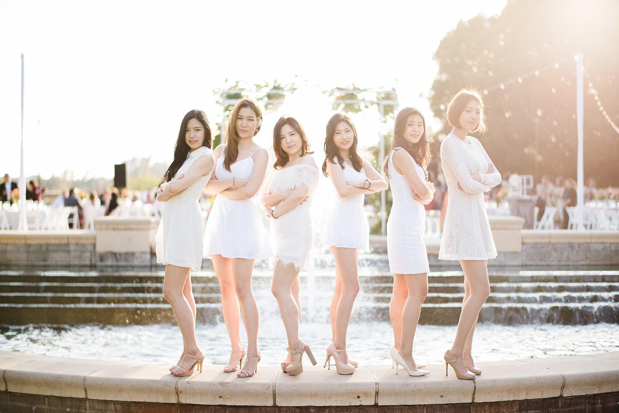 graduation senior portrait of korean girls doing a kpop pose in front of a fountain with a beautiful sunset in the background at ucla in los angeles