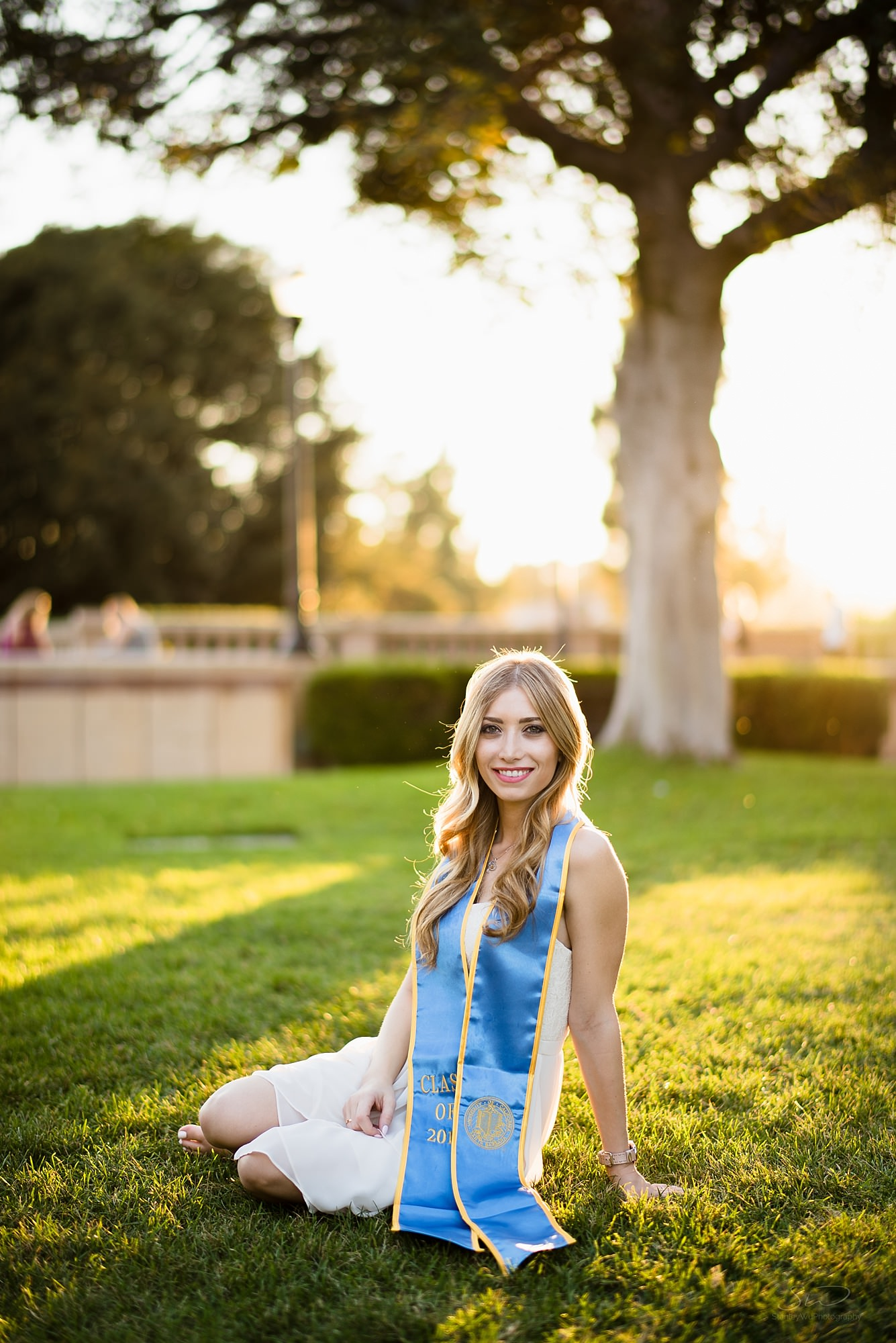 beautiful graduation senior portrait of a white girl in a white dress sitting on grass in front of a beautiful sunset at ucla in los angeles