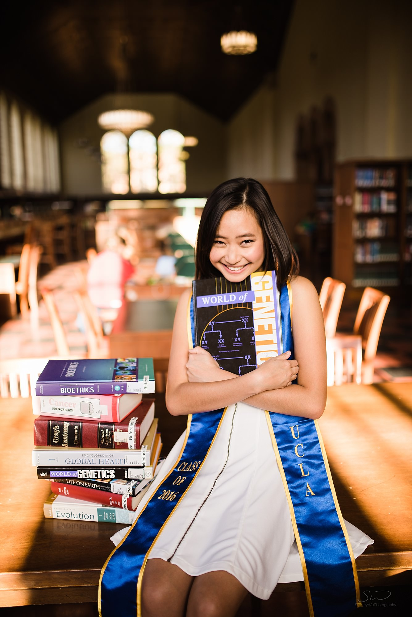cute graduation senior portrait of a girl holding library books happily at powell library at ucla in los angeles