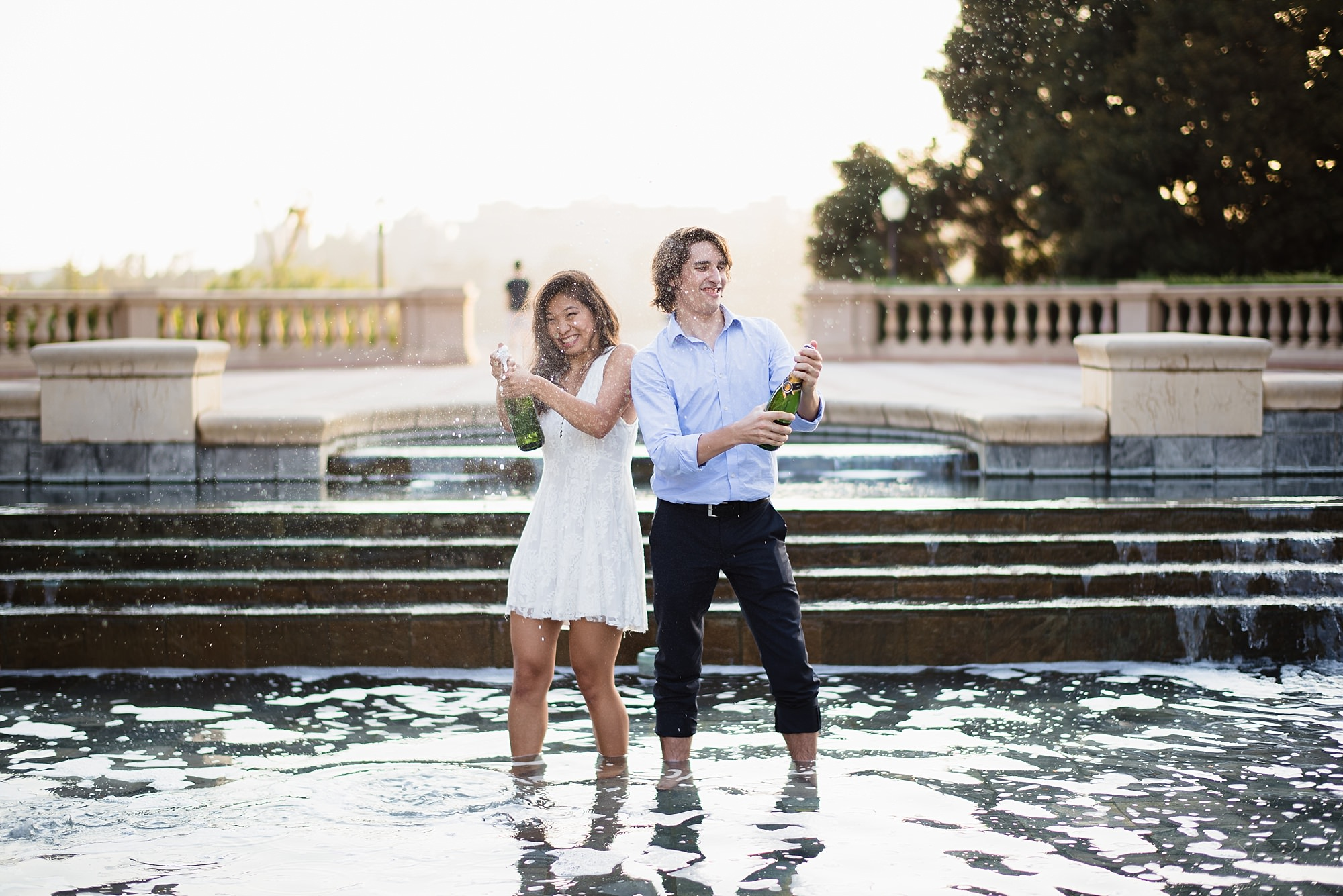 cute and fun graduation senior portrait of a couple popping champagne bottles in shapiro fountain during sunset at ucla in los angeles