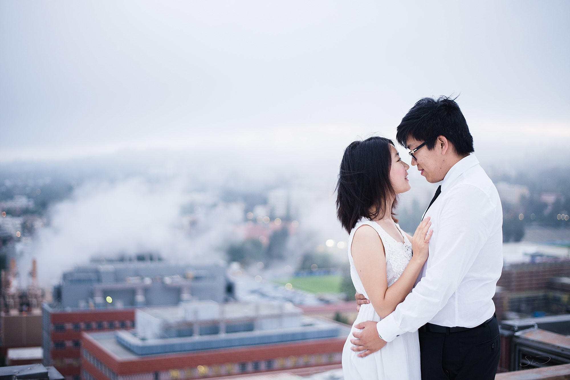 graduation senior portrait of a couple having a beautiful moment on a rooftop with some epic fog in the background at ucla in los angeles