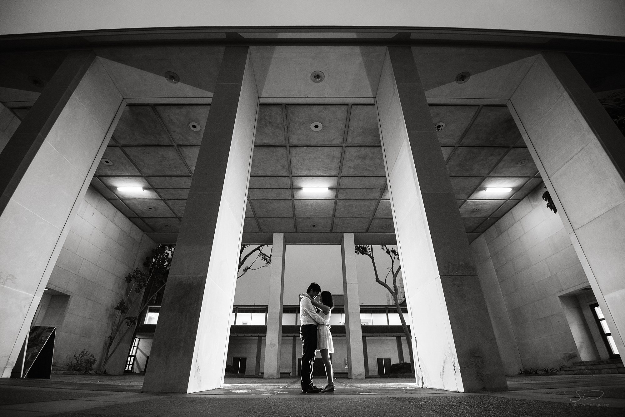 edgy contrasty black and white graduation senior portrait and ultrawide shot of a couple standing and embracing each other at ucla in los angeles