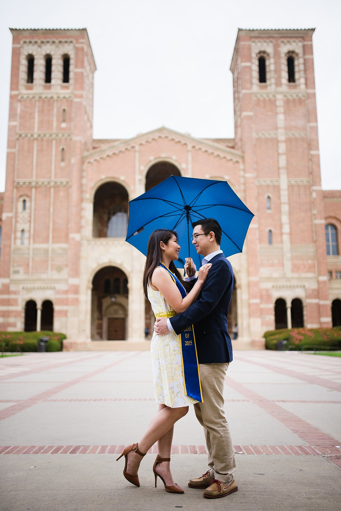 beautiful artistic graduation senior portrait of a couple holding umbrella in front of royce hall at ucla in los angeles