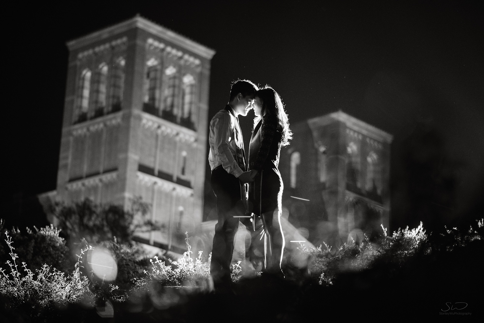 dramatic graduation senior portrait of a couple lit by flash at night in front of royce hall in black and white at ucla in los angeles
