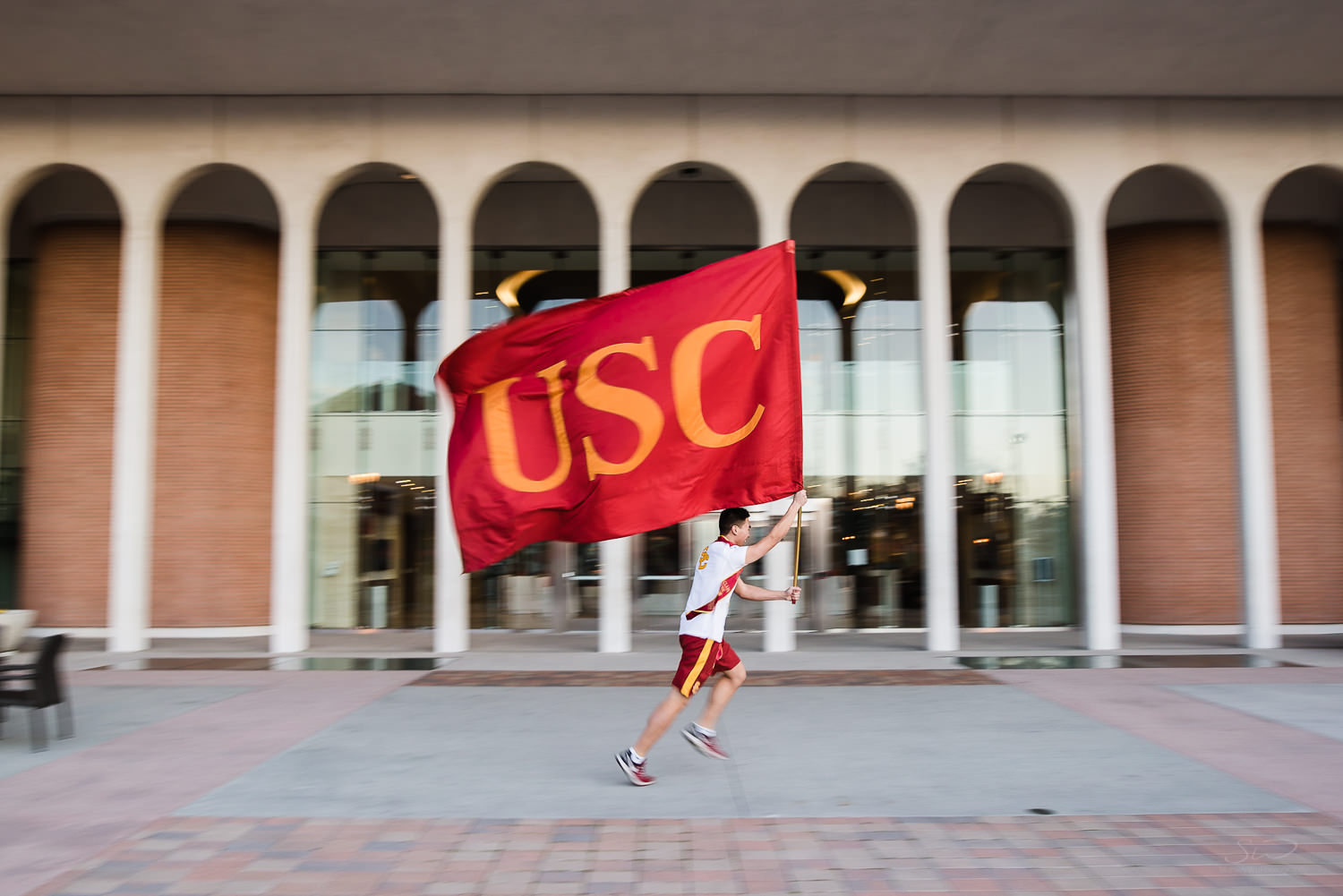 USC college senior graduate motion blurred running with USC flag by Stanley Wu Photography | Portrait & Wedding Photographer serving Los Angeles, Orange County, and Southern California