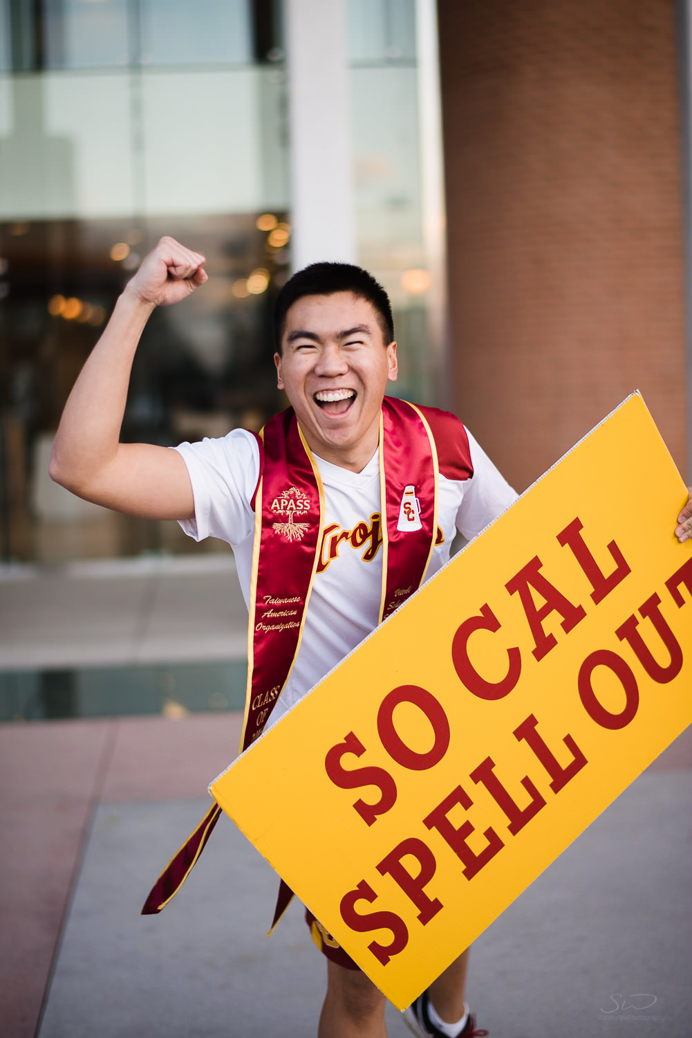 USC college senior graduate posing with spirit team sign by Stanley Wu Photography | Portrait & Wedding Photographer serving Los Angeles, Orange County, and Southern California