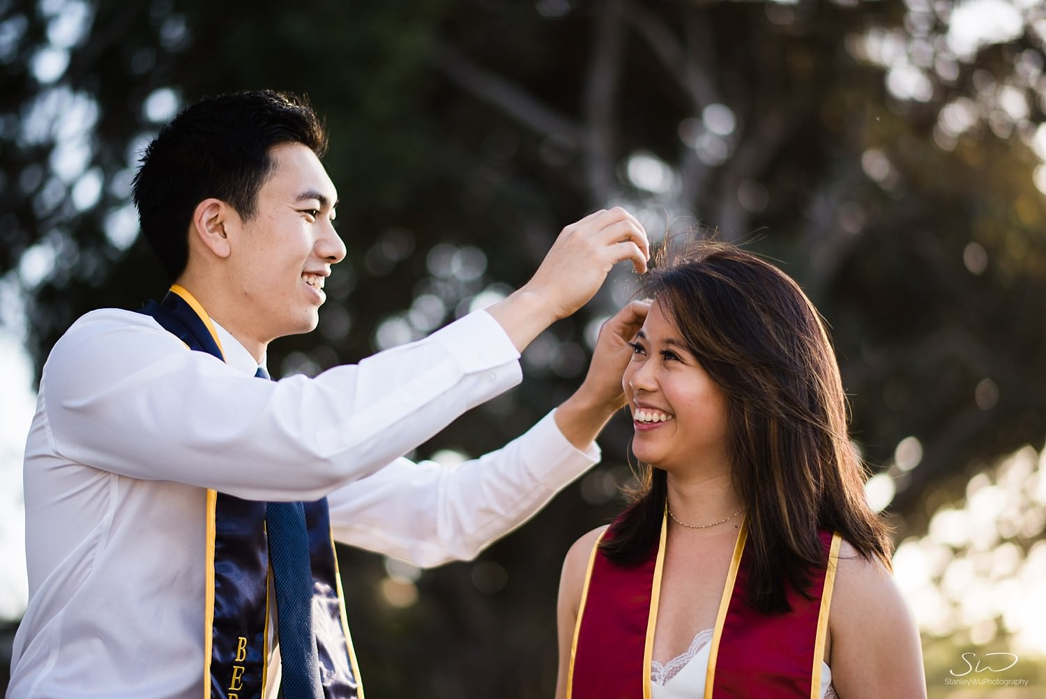 Couple from USC and UC Berkeley wearing sashes fixing hair | Los Angeles Graduation and Senior Portrait Photographer