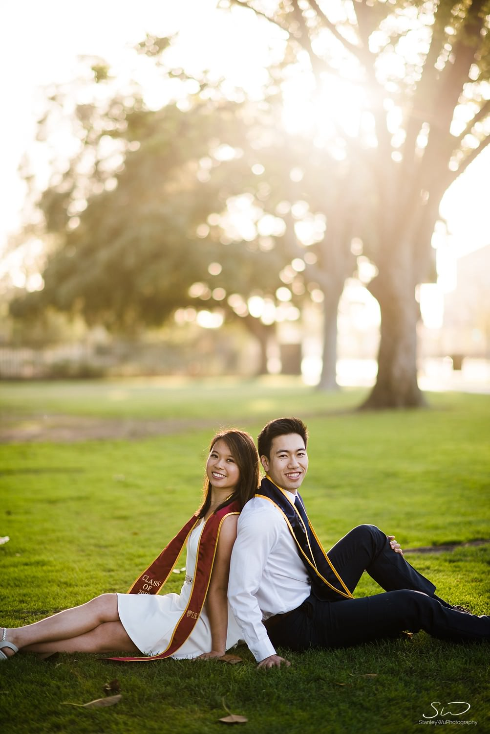 USC and UC Berkeley senior couple sitting together on grass  | Los Angeles Graduation and Senior Portrait Photographer