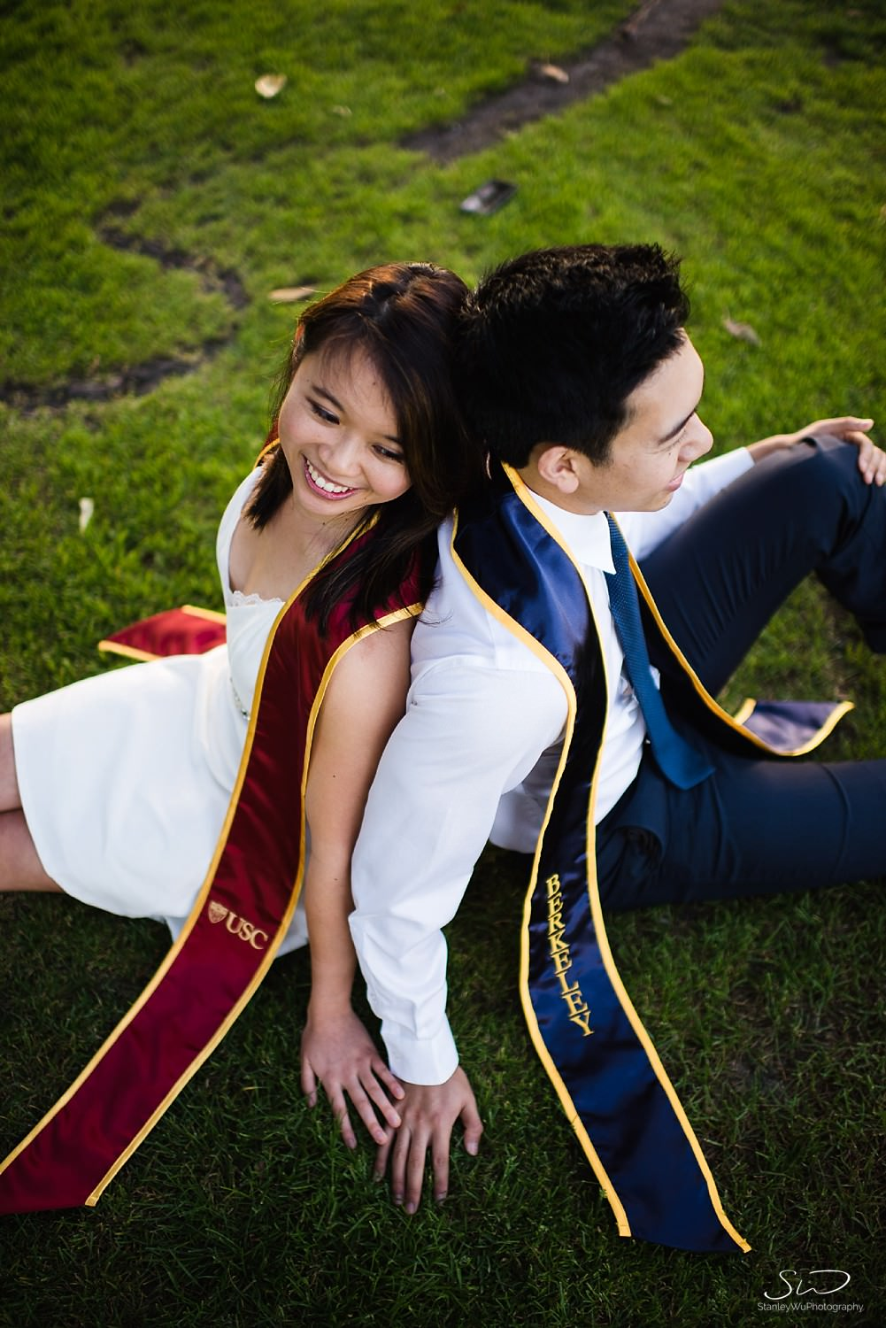 UC Berkeley and USC couple sitting on grass | Los Angeles Graduation and Senior Portrait Photographer