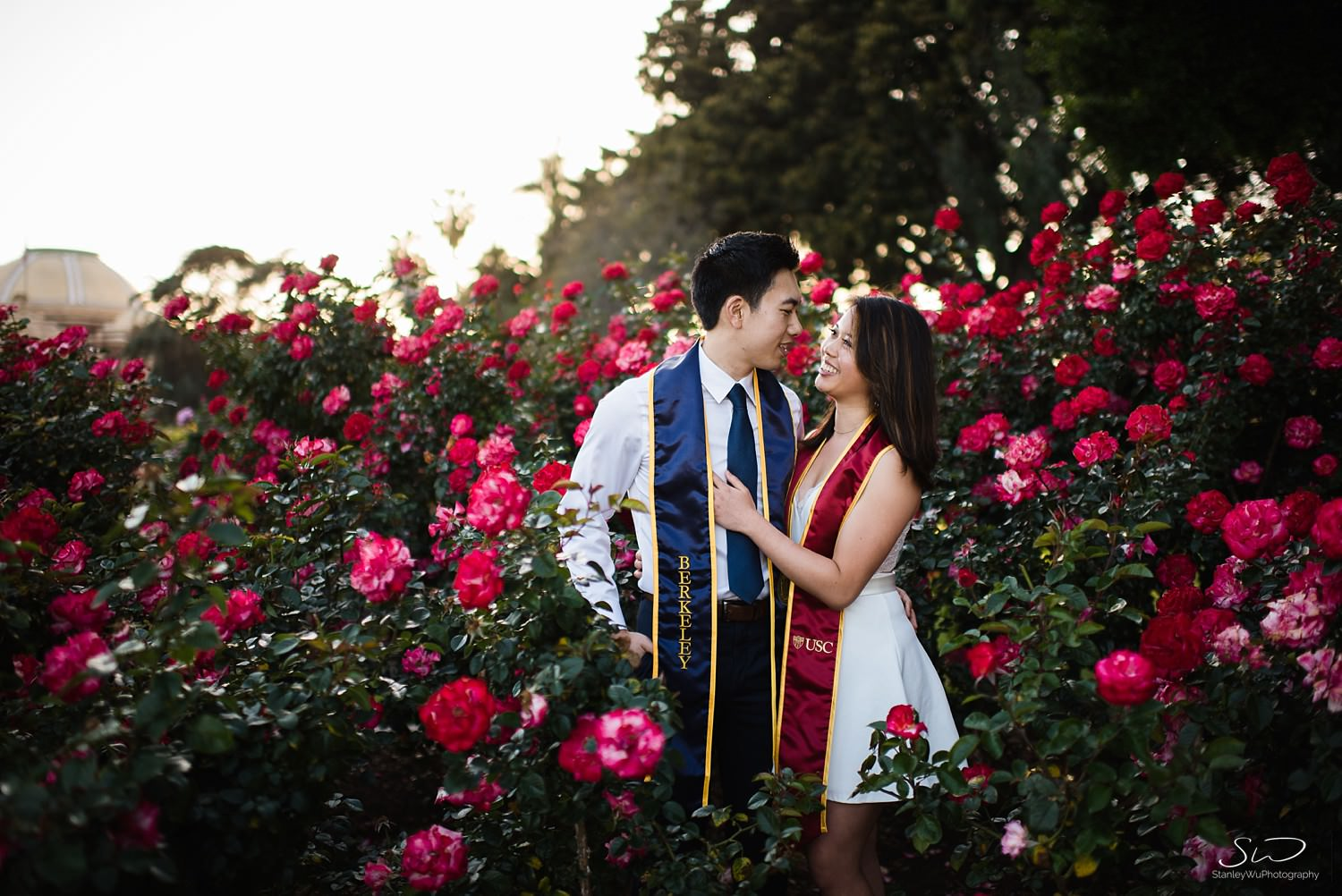 USC and UC Berkeley couple hugging in Rose Garden at USC  | Los Angeles Graduation and Senior Portrait Photographer