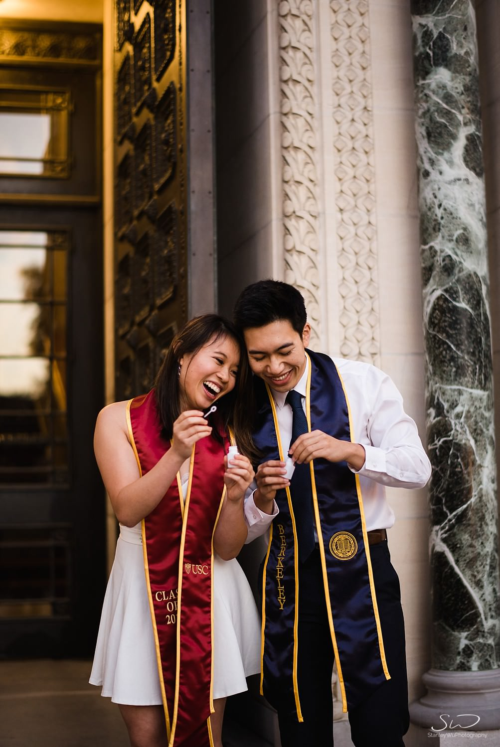 USC and UC Berkeley couple holding bubbles while wearing graduation sash UC Berkeley senior Facetiming in front of Doheny Library | Los Angeles Graduation and Senior Portrait Photographer
