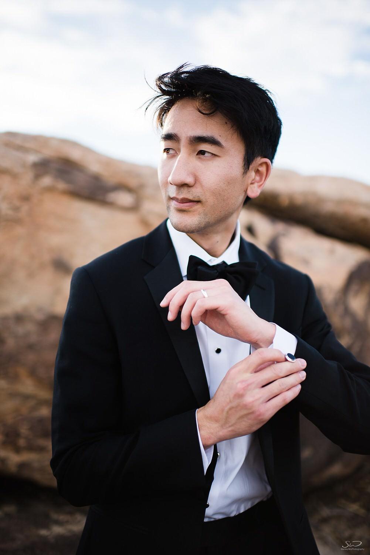 Groom getting ready buttoning sleeves  | Joshua Tree Desert Wedding, Engagement, Elopement Inspiration