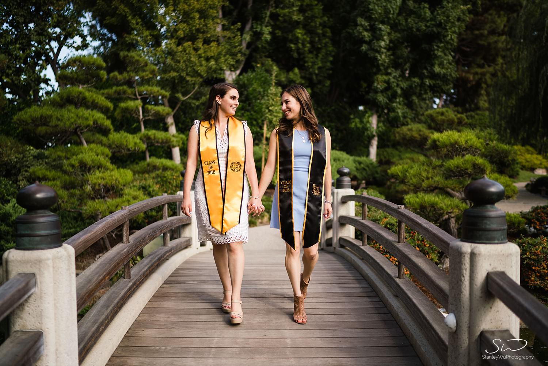 two girls walking hand in hand on a bridge graduation portraits at csulb earl burns miller japanese garden