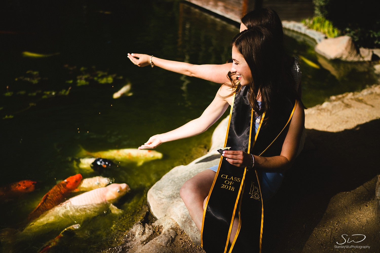 two girls feeding koi fish graduation portraits at csulb earl burns miller japanese garden