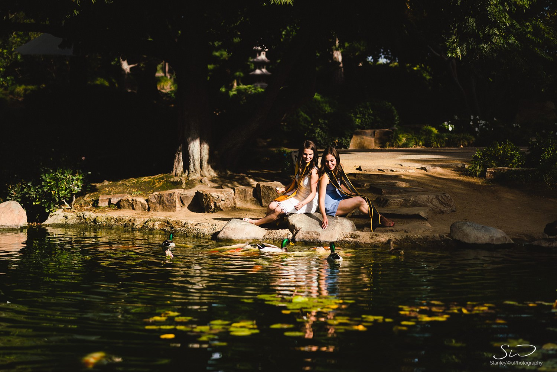 two girls sitting under a tree feeding fish graduation portraits at csulb earl burns miller japanese garden