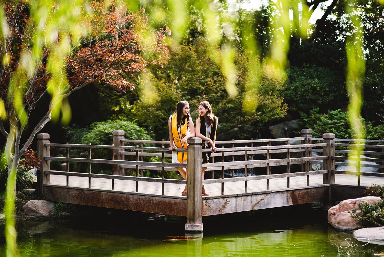 two girls smiling on a bridge graduation portraits at csulb earl burns miller japanese garden