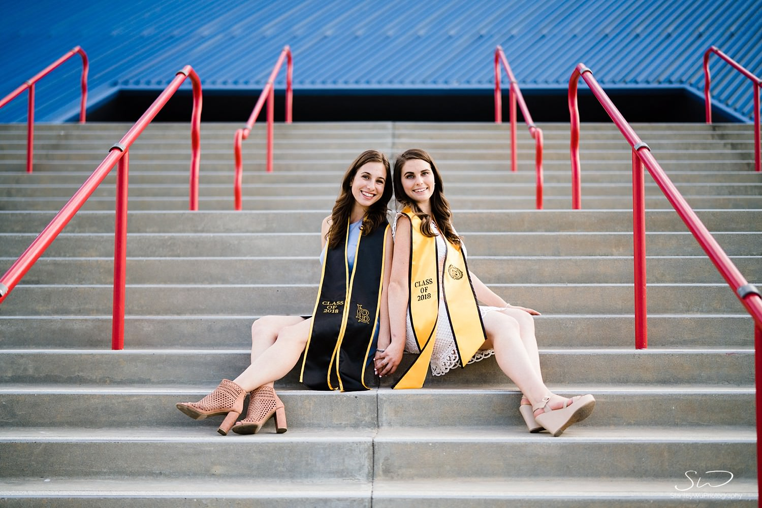 twin sisters sitting back to back graduation portraits at csulb pyramid