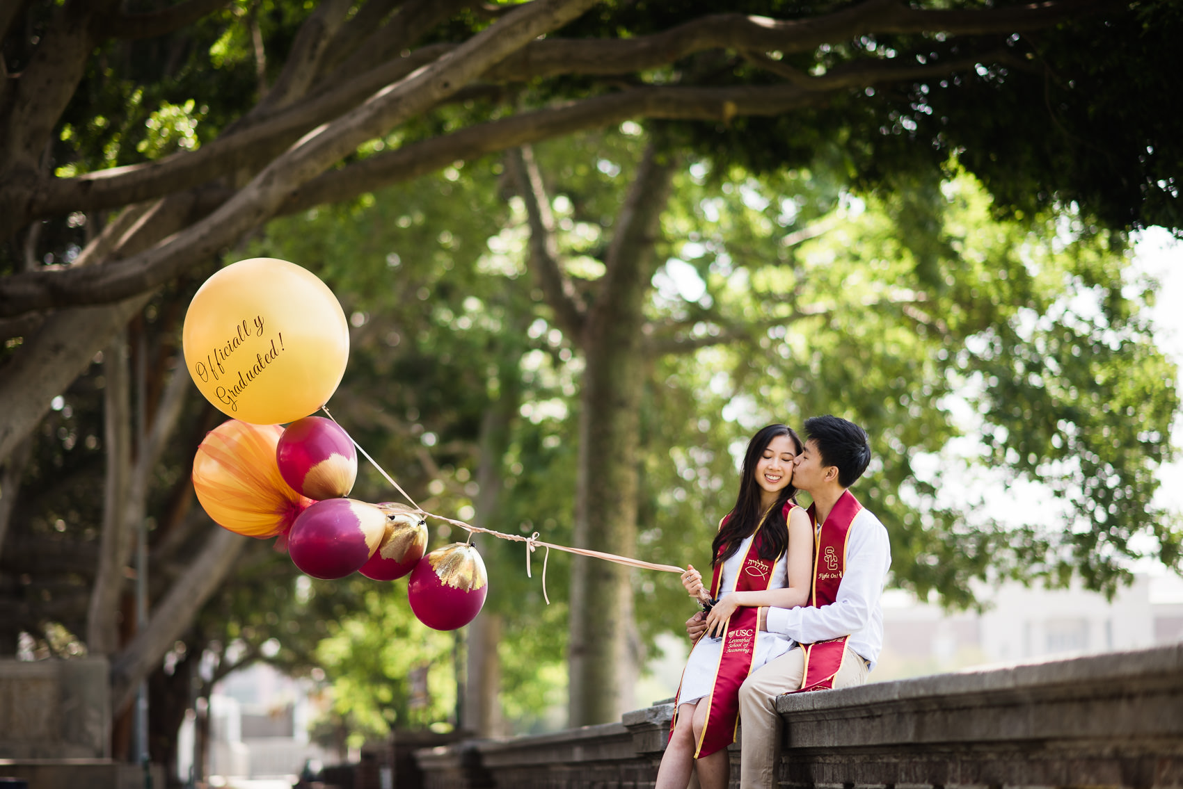 portrait of a graduating couple with celebratory balloons kissing at usc by the rose garden
