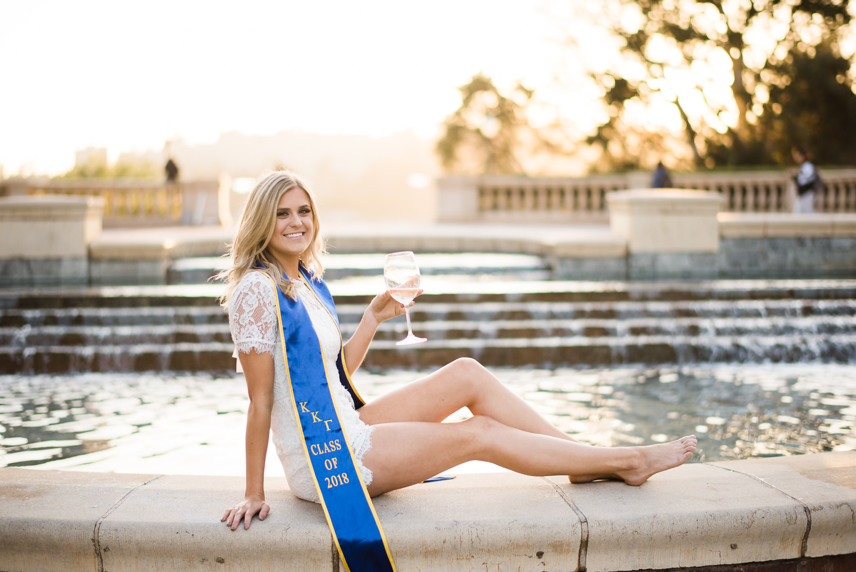 portrait of a sommelier girl holding a wine glass in graduation apparel at ucla shapiro fountain