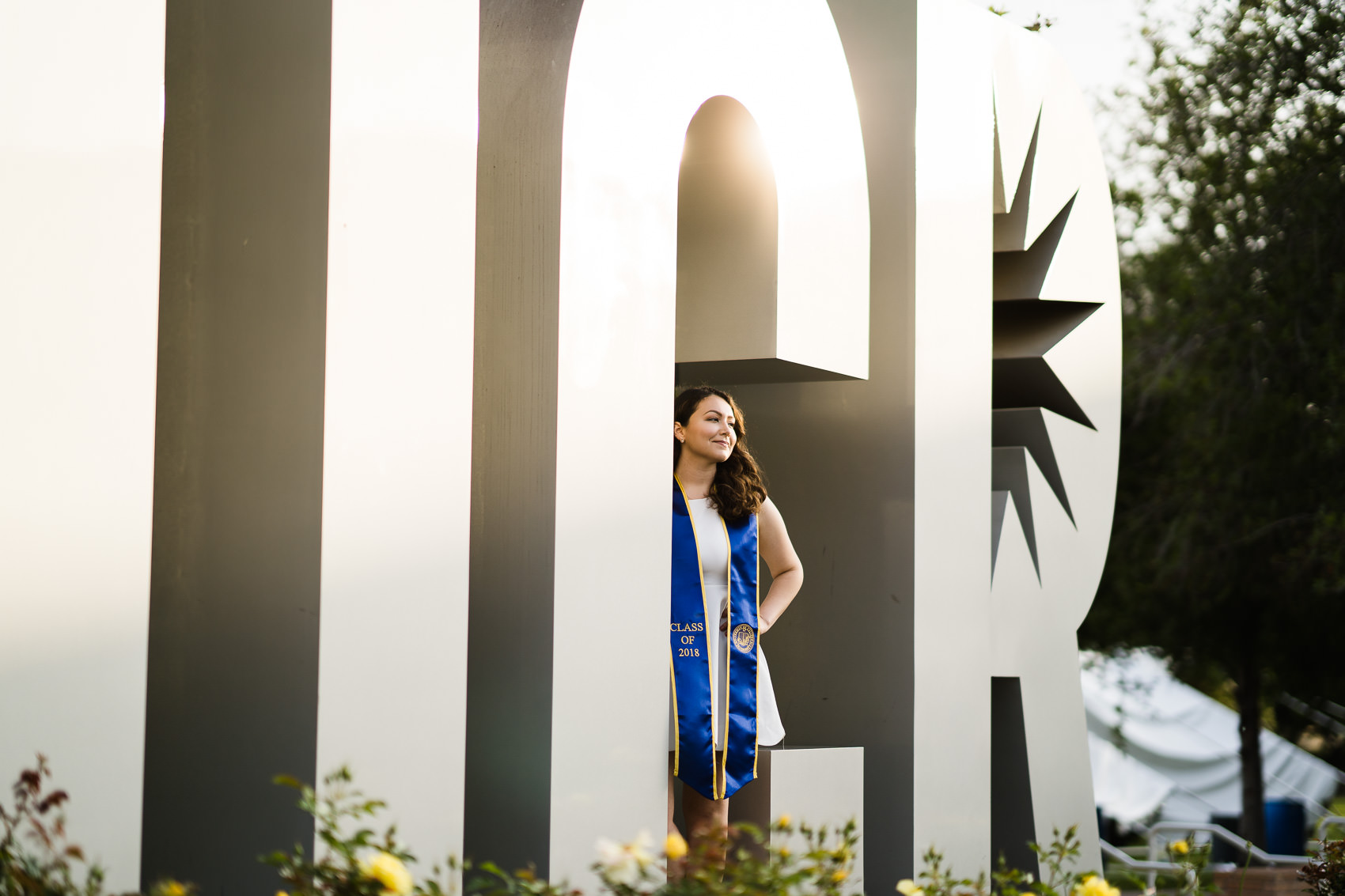 portrait of a girl in graduation apparel looking off into the distance standing in the uc riverside sign