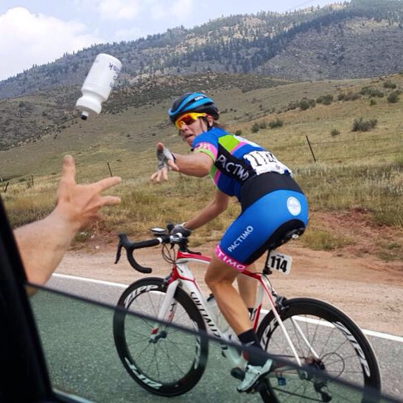 Kids - don't try this at home. Jennifer is tossing a bottle back to Alison in the follow car at last year's Pro Challenge. (She caught it!)