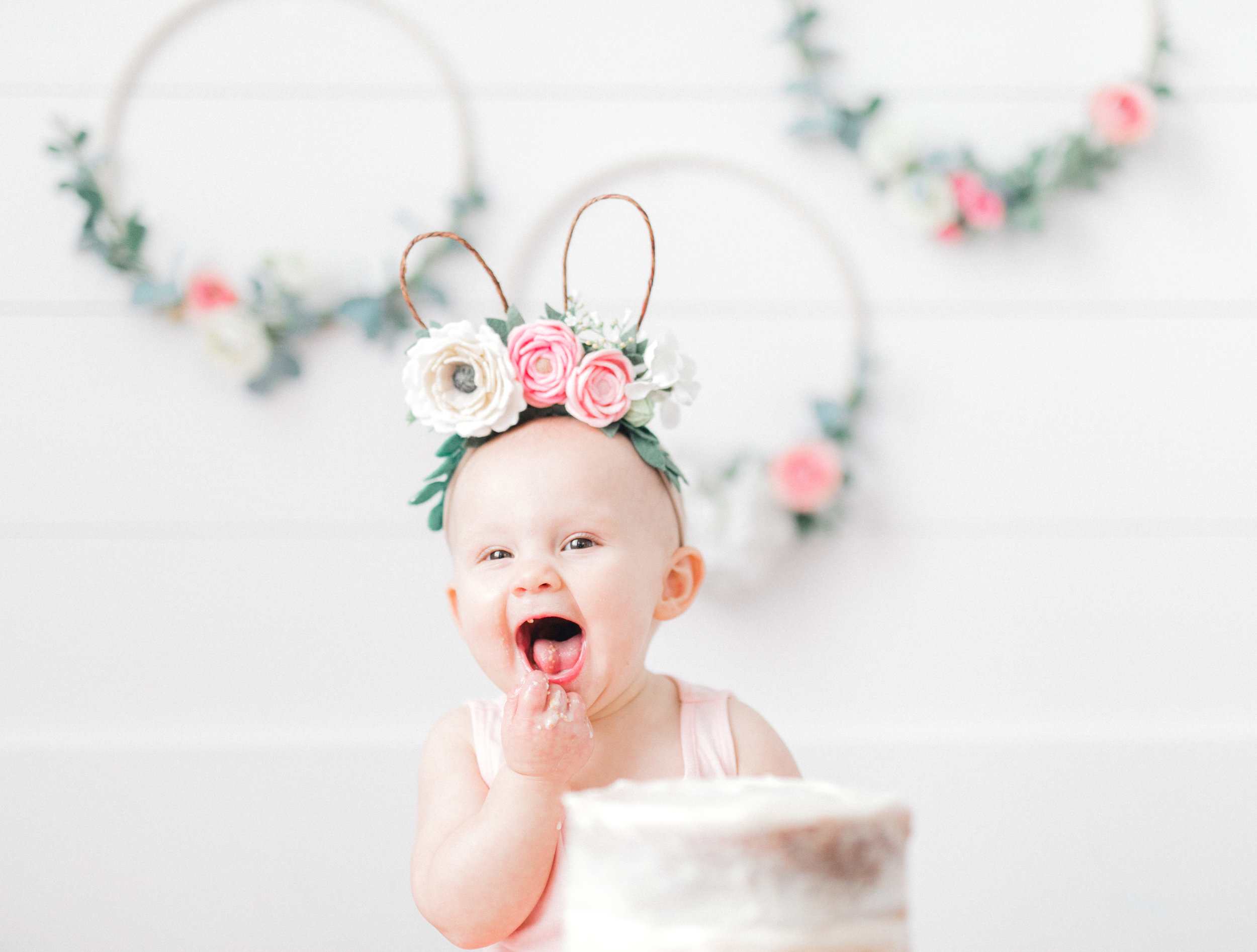 """Hi friends! This is my first personal blog post, but I am so excited to share this one with you all because it is all about my sweet girl and our family these past few weeks as we celebrated her first birthday! I have always heard people say that time goes by so quickly when you have children, and y'all, they are not lying. I don't know how this past year went by so fast, but here we are and I have a one-year-old! I'm a ball of mixed emotions just thinking about it. I miss my tiny baby girl, but I love watching Anna grow into the sweet, sassy, and funny little girl that she is.  I knew I wanted to do a blog post about Anna's party so that I could give credit to all the people who helped make it so special (because yes, I'm crazy, and I used a lot of my talented friends to help pull it off). The inspiration for the party came from Anna's birth date; she was born on Easter Sunday of last year, so I knew that I wanted to do something with bunnies. Bunnies have always been her theme, and we've called her our """"Little Bunny Girl,"""" so that's where I drew inspiration. Once I started looking online at bunny parties, I had a hard time figuring out which direction I wanted to go because there is A LOT of stuff out there and a lot of different decorations and bunnies! The first decorations that came together were the floral hoops (I saw them some somewhere online). I asked my friend from Covenant Threads to make them and I was blown away. Once I had the hoops, they acted as the centerpiece for everything else (the cake topper, the headbands, the flowers).  I'll give you fair warning now… if you continue to scroll through this post, there are A LOT of pictures. The weeks leading up to it and the week of Anna's birthday, I took pictures of some of the decorations for the party and we had pictures taken of the party, a cake smash session, and one-year family photos. According to my Instagram poll, you all wanted to see """"ALL THE THINGS""""…so that's what I'll show you! I'll also put a"""