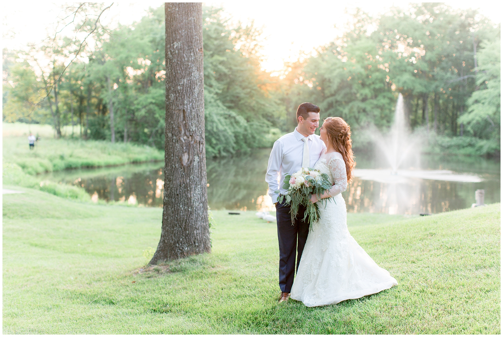 "Trey and Leslie Schweitzer had a sunny, daytime wedding on June 6, 2018. Burdoc Farms had a beautiful gazebo for the ceremony and The Keith Glen, a beautiful new addition to Burdoc Farms. The venue is in the woods by a pond with a lighted fountain, surrounded by fields and forest. With a more modern look and feel you can still enjoy the natural beauty of Burdoc Farms because of the wall of glass that faces the pond and woods. Chandeliers, a copper bar top, natural wood farm tables and natural stone fireplace adds to the beauty of the building..  Leslie and Trey's engagement story was a part of a family tradition. During an annual Easter egg hunt, Regan, Leslie's dog, ran up to her with something shiny dangling off his collar. Trey kneeled and popped the question with all of Leslie's family watching, just the way she had always imagined!  Leslie's engagement ring is stunning, it's a marquise cut with circle emeralds on each side. Her wedding dress was from David's Bridal and is form fitting, with a sheer top and sleeves. The lace embellishments on the sleeves and her swept back half up-do gave her the perfect bridal look.  Every detail in their wedding was planned with such perfection! The bridal party helped decorate the cake with the cutest greenery and succulents. The ceremony arch was so elegant with white flowers and greenery strewn around it. Trey and Leslie stood under that arch holding in their hearts what they loved most about each other and said, ""We do!""  At the very end of the wedding, Trey and Leslie were able to have a short photo session with the sunset in the background sharing an intimate time after a hectic day!"