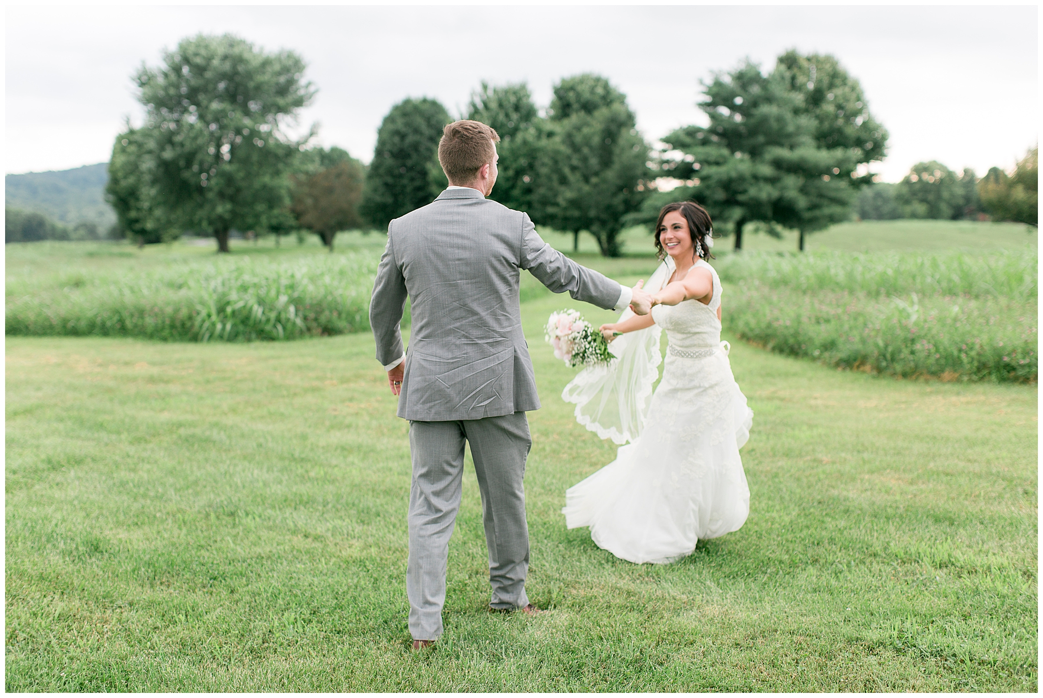 "Danville Kentucky was the dreamy backdrop for Mackenzie and Bradley's July ""I dos."" This couple had months to plan their perfect day, but the venue change the day before threw them for a loop! Nobody could have pulled in off as flawlessly as this perfect couple and their awesome bridal crew!     It's all in the details with this unique barn wedding. The ceremony arch was wrapped with white silk, eucalyptus, and beautiful flowers waiting for the even more stunning bride. Mackenzie wore a lace dress with a sweetheart neckline from David's Bridal and had a custom-made veil pinned in her curls. The bridesmaids (yes, there were a lot!) wore shades of green to compliment the grey suits worn by the groomsmen.     Bradley's reaction to Mackenzie walking down the aisle was so precious; all the family members were tearing up! The night was spent capturing every single sweet moment between the two of them. They made sure to include tons of time for dancing so the floor was filled with laughing and fun until the final send off. As everyone blew bubbles in the happy couples way, they drove off and started their lives together."
