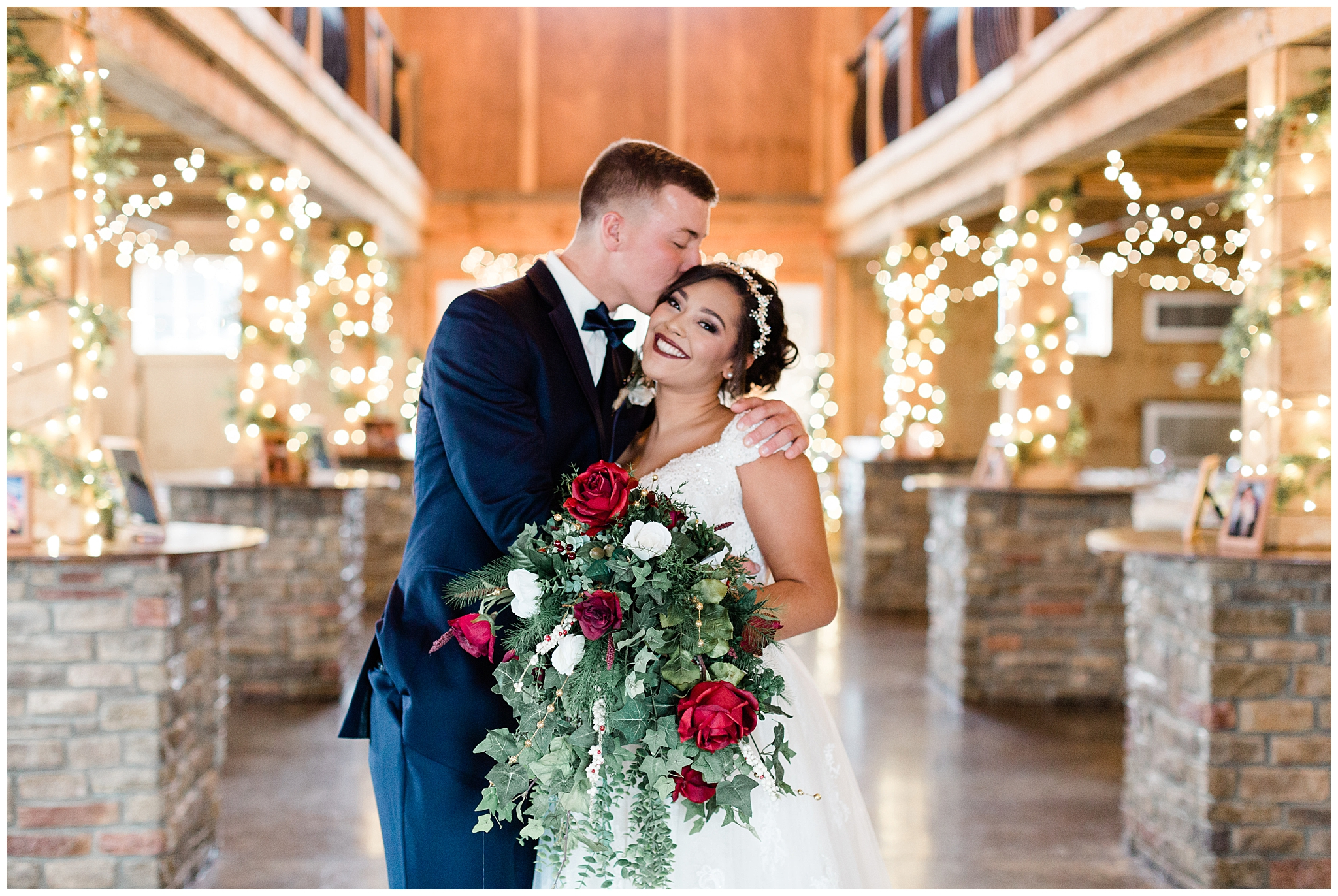 The Adkin's wedding was decked out in douglas fir and christmas lights at  The Josephina Event Venue . Dana's bouquet was filled with deep red roses and fluffed with greenery. Her dress was a stunning ivory with lace embellishments at the top, which complimented her lace and beaded headband.    The bridesmaids got ready in seasonal flannels while the groomsmen pinned on their pinecone corsages. The ceremony was held at Knoxville Baptist Church which was adorned with wreaths, garland and a massive christmas tree. The bridal squad walked down the aisle in gorgeous David's Bridal, maroon, lace top dresses.    The ceremony was held in a huge, white barn with high rafters. Lights were wrapped around the wood and stone poles and a chandelier hung in the middle of the dance floor. The Adkin's ended the night dancing while being surrounded by those they love most!