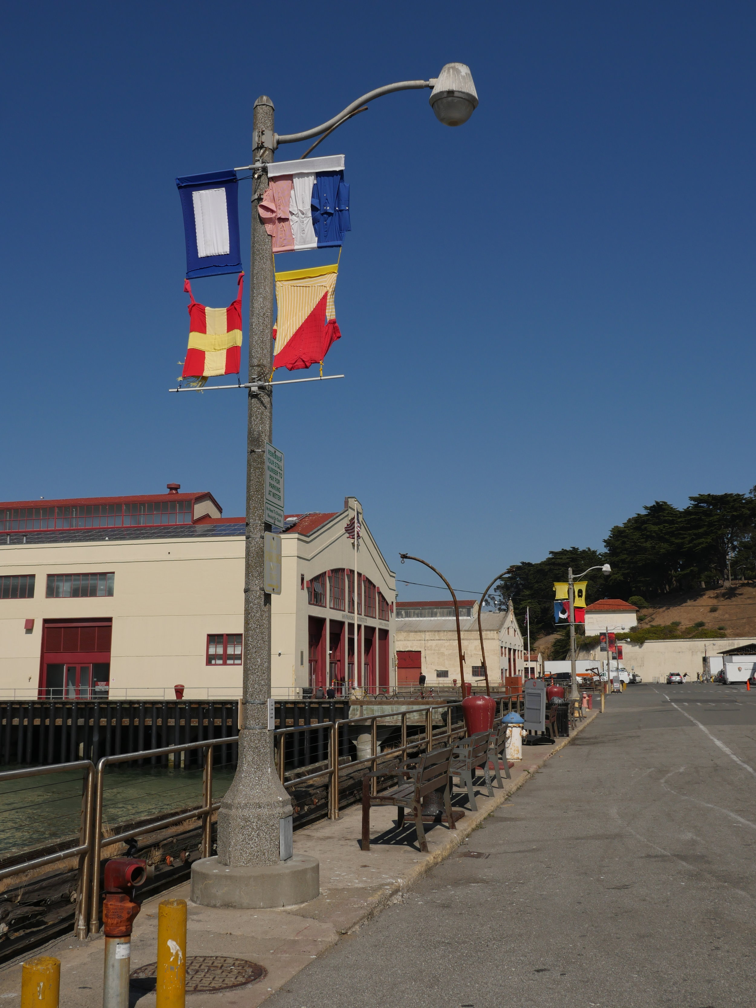 Hand-sewn signal flags installed on lampposts overlooking the bay