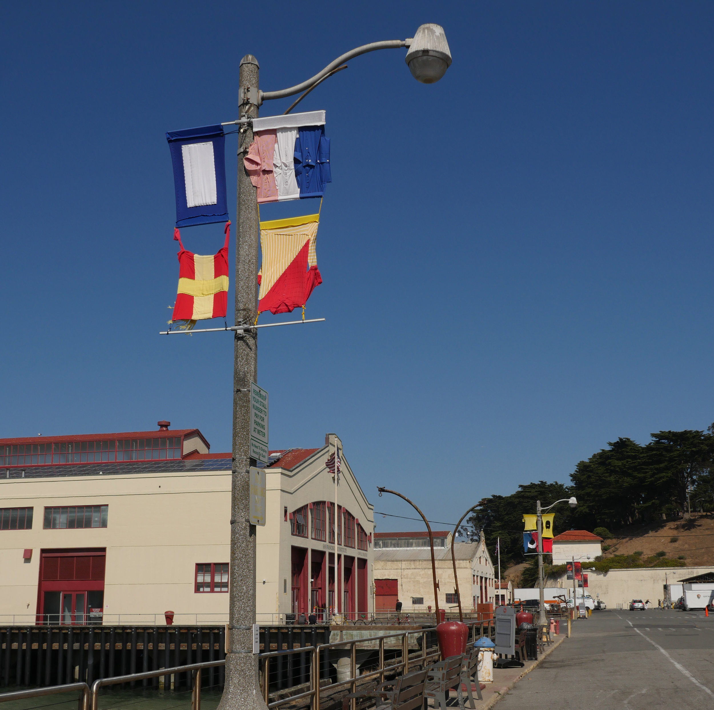 Signal flags made from discarded clothing, installed on lampposts overlooking the bay