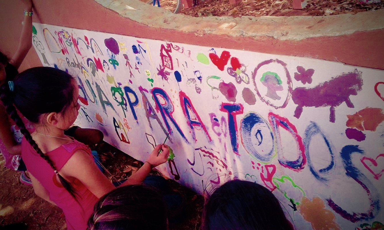 """Kids painting a mural that says """"Agua Para Todos"""" or water for everyone."""