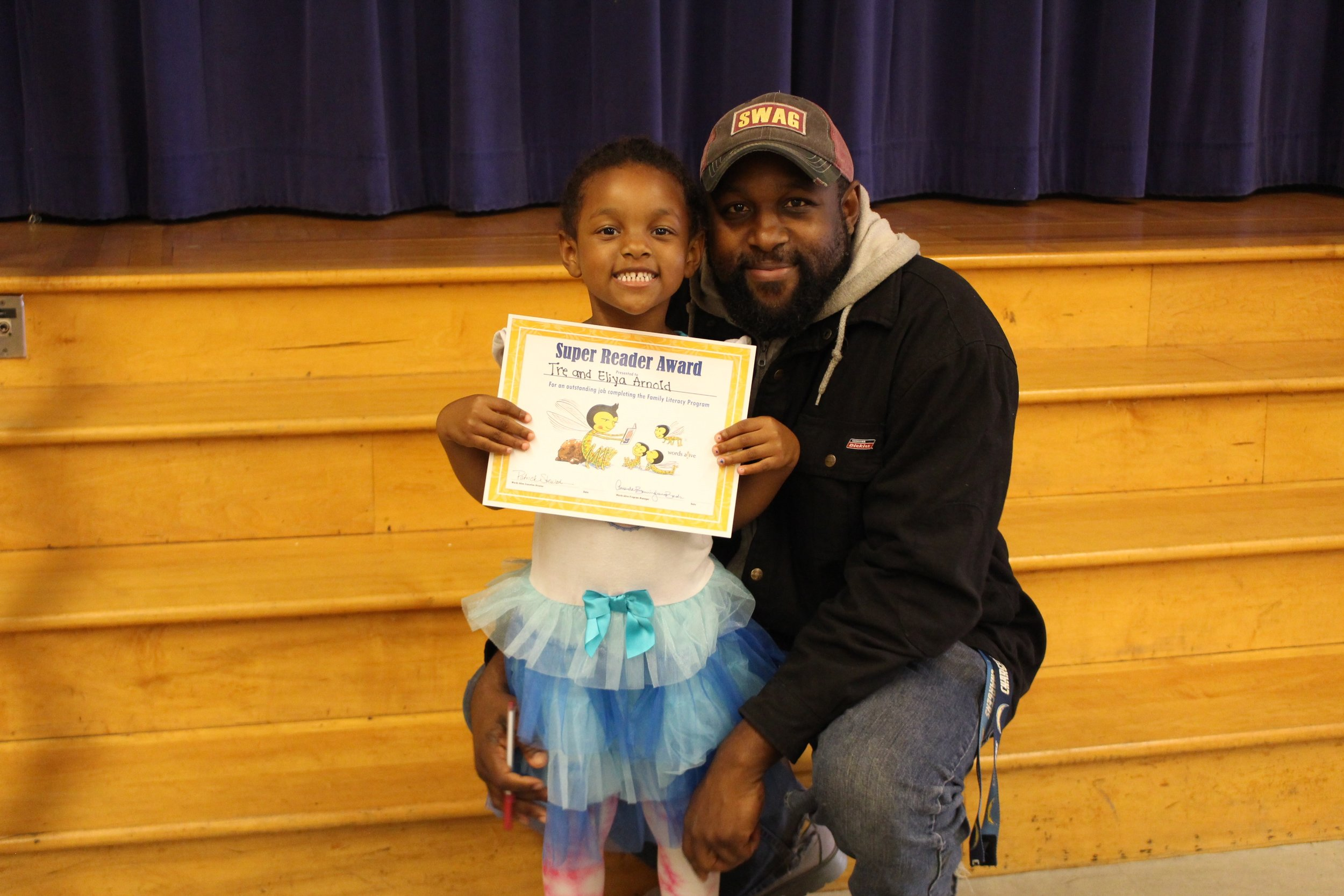 """Tre (single father of three, Army veteran,community college student) with his child at a Family Literacy Program graduation in 2016. His daughter is holding a piece of paper that says """"Super Reader Award."""" Tre had perfect attendance during the Family Literacy Program and said: """"I have learned so many different ways to get involved with my kid's life through reading. This experience has changed my life and my kids enjoy reading with me so much."""""""