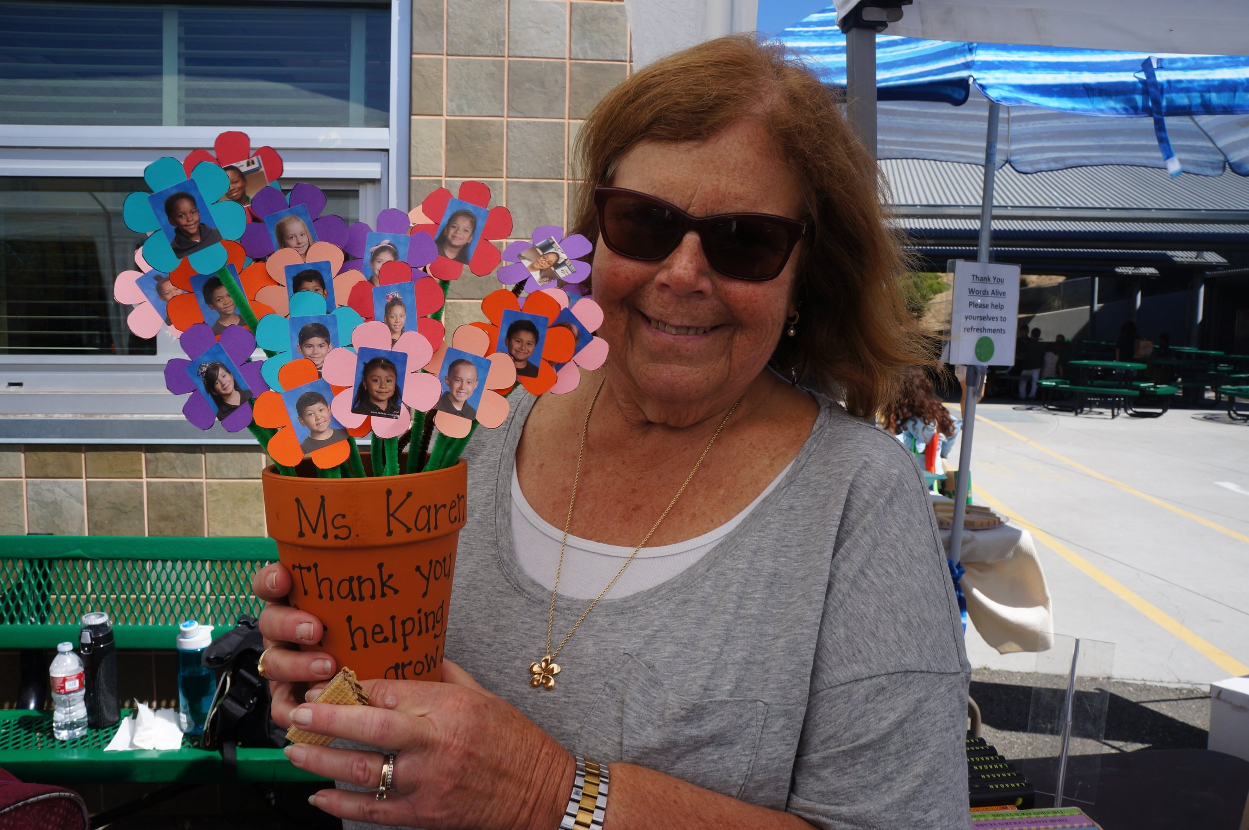 "Picture of long-time Words Alive volunteer Karen Malin holding a flower pot craft containing pictures of the students she reads to! The flower pot says, ""Ms. Karen, thank you for helping us grow."""