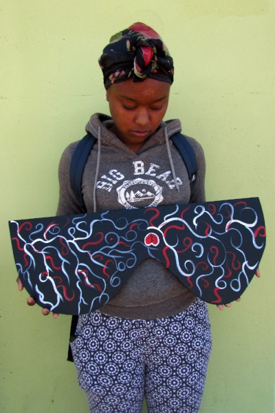 "An image of a student from Monarch holding her piece of the communal sculpture. Her piece was based around the theme, ""grief."""