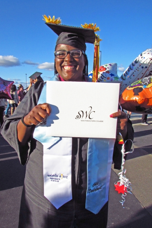 An image of Domminiece at her graduation. She's holding her Southwestern College degree up to the camera and smiling, and she's wearing a Words Alive Westreich Scholar stole!