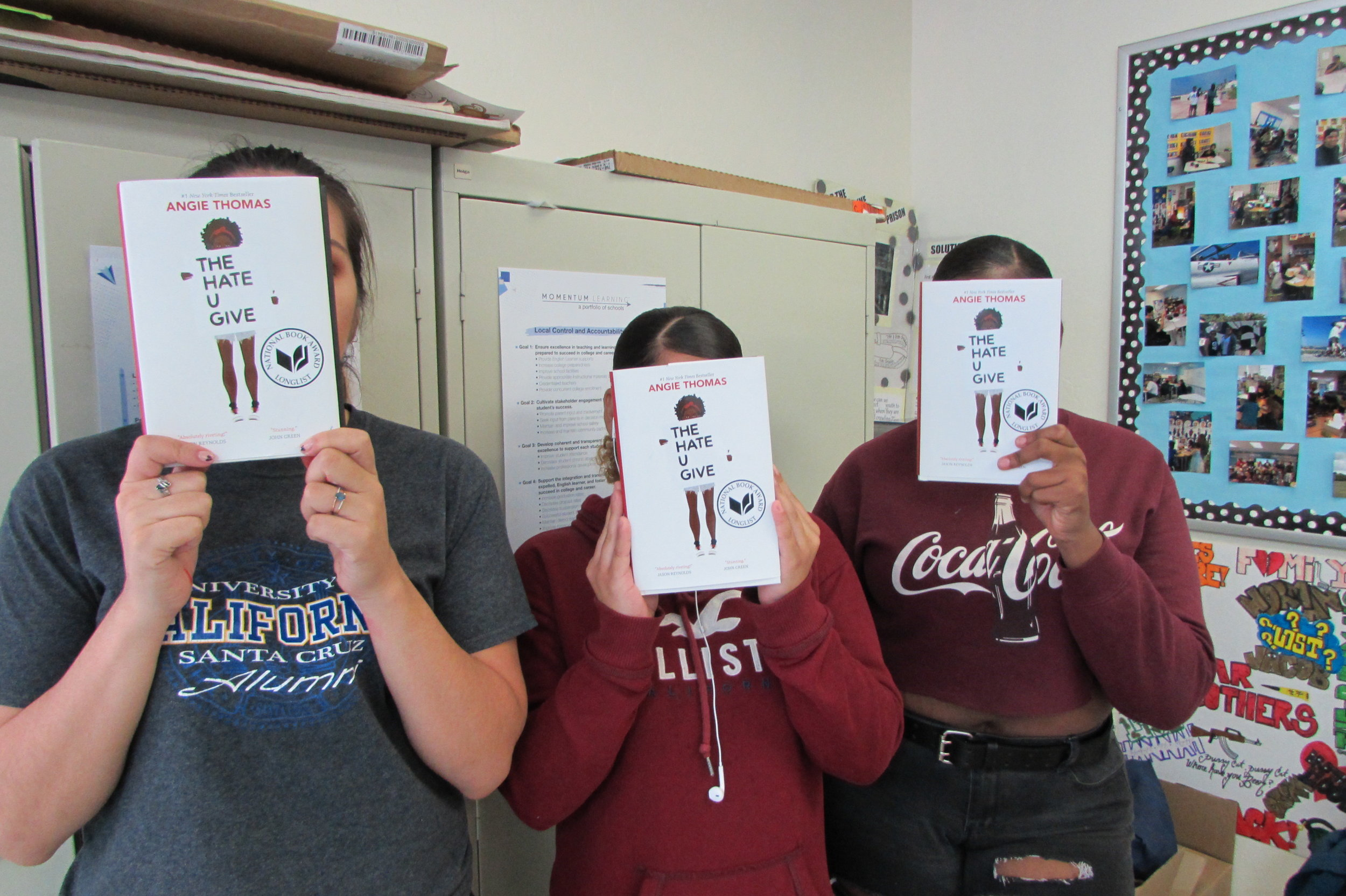"""An image of three of our Adolescent Book Group students holding up copies of the YA novel """"The Hate U Give"""" to cover their faces."""