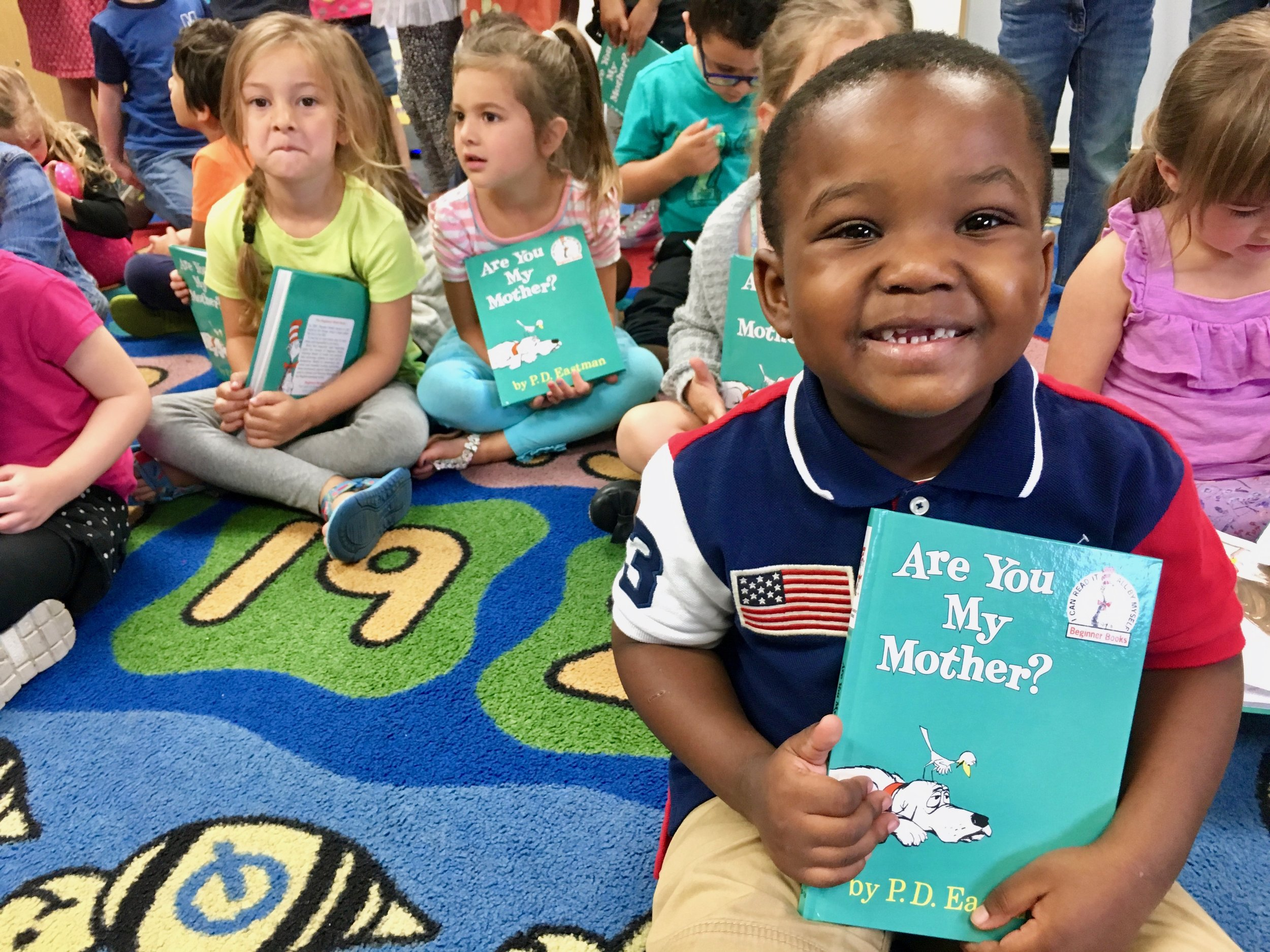 "A picture of a child in our Read Aloud Program holding the book ""Are You My Mother?"" while smiling."