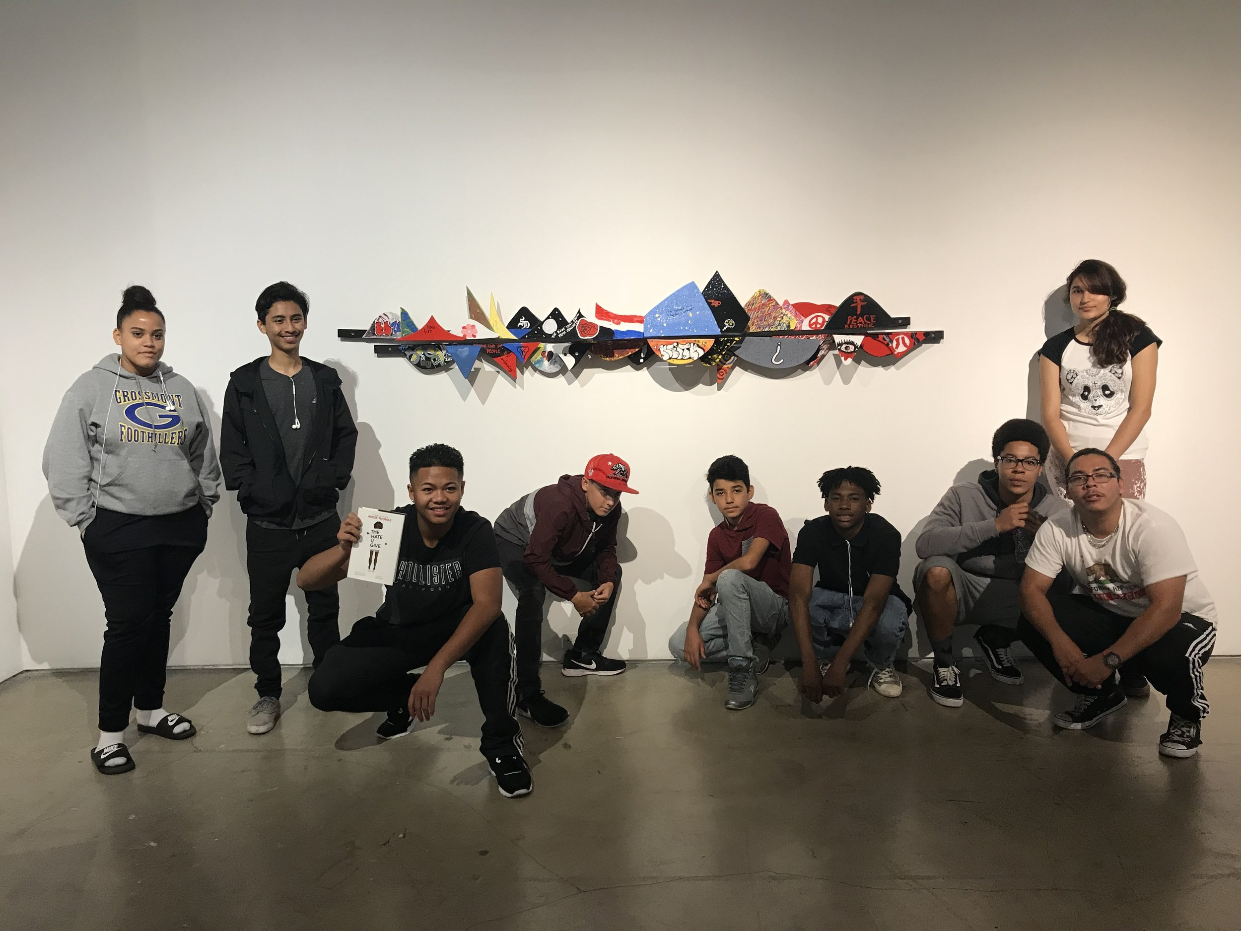 An image of our students from La Mesa Community School posed in front of their sculpture. One of the students is holding up a copy of the book, The Hate U Give.