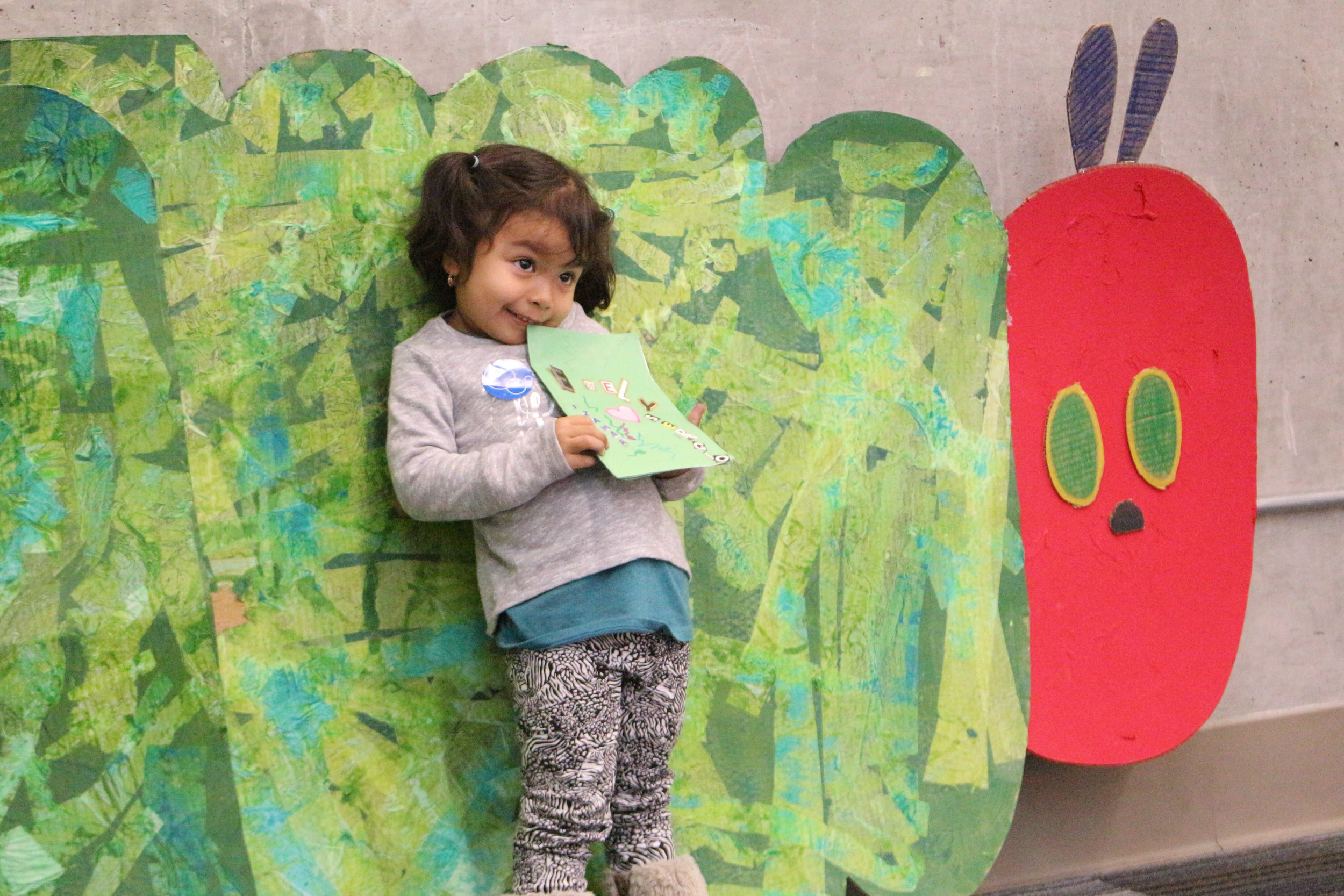 An image of one of the kids in our Family Literacy Program standing in front of a huge cutout of the Hungry caterpillar!