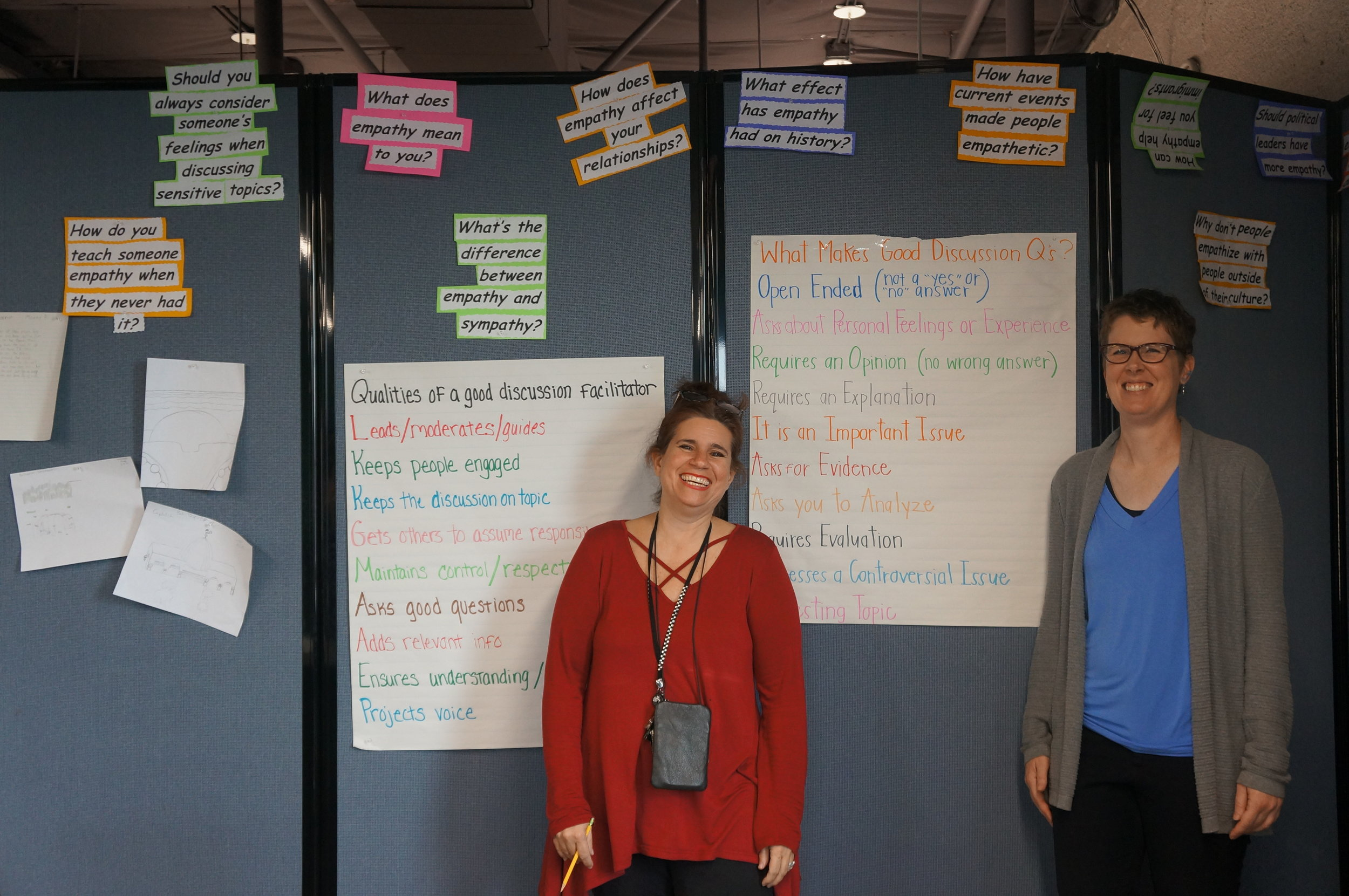 Teachers from the school site 37ECB stand in front of posters about facilitation tips that the students created together. Their semester culminated in a project in which the students were in charge of facilitating discussions.