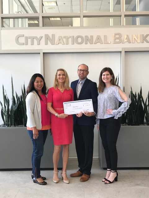 An image of Words Alive Executive Director, Patrick Stewart, and Volunteer Program Manager, Christina Meeker, with representatives from City National Bank.